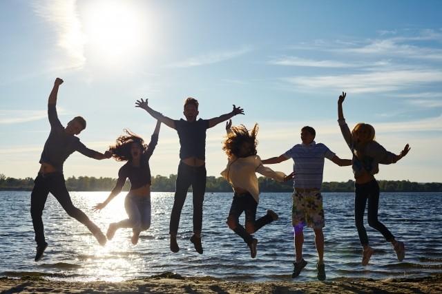 水辺でジャンプする健康そうな若者たち
