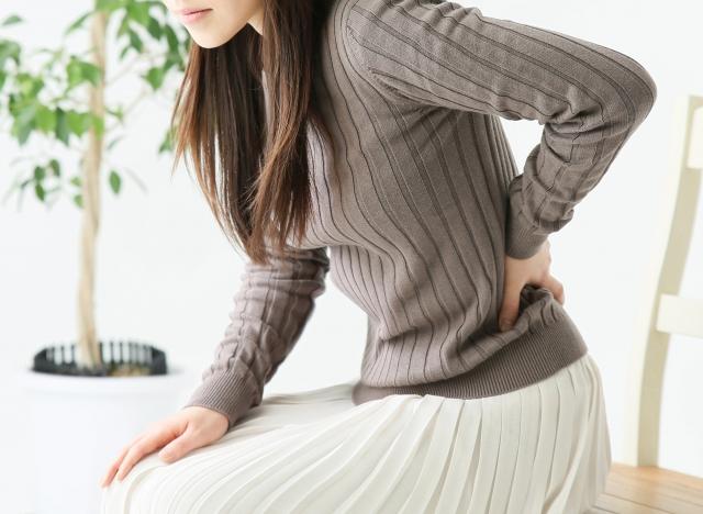 腰が痛そうな女性